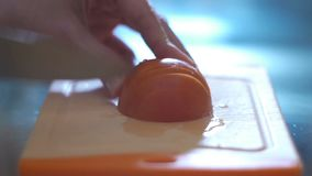 Hand cutting tomato in a kitchen stock video footage