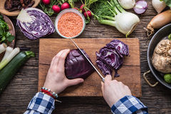 Hand cutting vegetables.Women hands is slicing cabbage on wooden board near vegetables.  Stock Photo