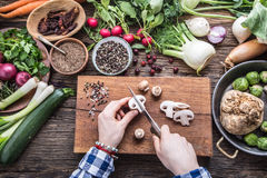 Hand cutting vegetables.Women hands is slicing mushrooms on wooden board near vegetables. Royalty Free Stock Photography