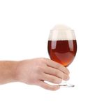 Hand with a dark beer glass. Stock Image