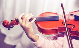 A hand dark skinned little girl using a violin while playing Royalty Free Stock Image