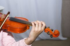 A hand dark skinned little girl using a violin while playing Stock Images
