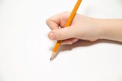 Hand das rigth des Kindes, die einen Bleistift an über Weiß hält Stockbild