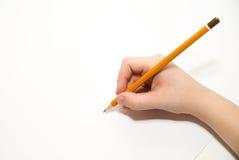 Hand das rigth des Kindes, die einen Bleistift an über Weiß hält Lizenzfreie Stockfotografie