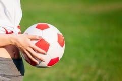 In hand de bal van het voetbal Het concept van het voetbalspel De ruimte van het exemplaar Close-up royalty-vrije stock afbeeldingen