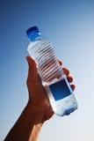 In hand de fles van het water stock foto