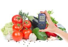 In hand de glucosemeter van het diabetesconcept en gezonde natuurvoeding stock fotografie