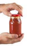 In hand de tomatenpuree van de kruik Stock Fotografie