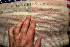 Hand on Declaration of independence 4th july 1776 on usa flag Royalty Free Stock Photo