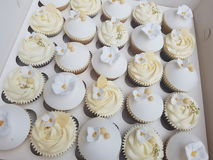 Hand decorated gold anniversary wedding cupcakes. Cupcakes which have been hand decorated with pears, edible gold dragees and hand made sugar flowers. Petunias royalty free stock photos