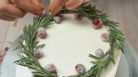 Hand decorates the cake with sugar cranberries. Hand of confectioner decorates the cake with sugar cranberries and rosemary stock video footage