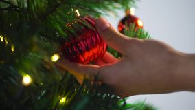 Hand decorating christmas tree with ball stock footage
