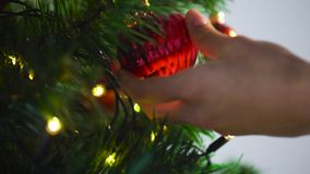 Hand decorating christmas tree with ball stock video