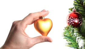 Hand decorating christmas tree with golden heart Stock Photos