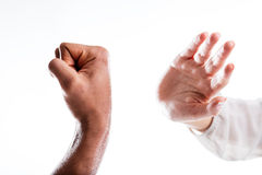 A hand defends from the punch that menaces it stock photos