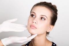 Hand& x27 del cosmetólogo; s que examina la cara femenina joven hermosa Imágenes de archivo libres de regalías