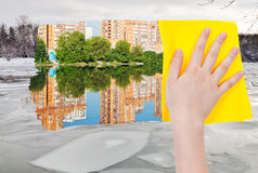 Hand deletes ice block in river by yellow cloth Stock Photos