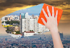 Hand deletes smog in city by orange cloth. Ecology concept - hand deletes smog in city by orange cloth from image and clear houses are appearing Royalty Free Stock Photography