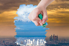 Hand deletes smog urban landscape by eraser. Weather concept - hand deletes smog urban landscape by eraser from image and clear blue city are appearing Stock Images