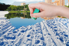 Hand deletes winter snow field by rubber eraser Royalty Free Stock Images