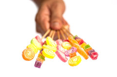 A hand delivering jelly sticks. Over white background Royalty Free Stock Photography
