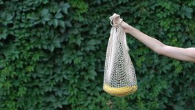 Hand demonstrating banana in crochet bag, reducing usage of plastic bags, reuse. Stock footage stock footage