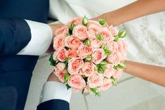 Hand in den Händen mit rosafarbenem Blumenstrauß Lizenzfreie Stockfotografie