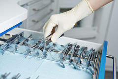 Hand of dentist reaching for dental tools Stock Image