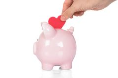 Hand deposit red heart in piggy bank Royalty Free Stock Photography