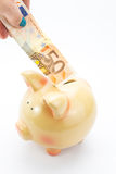 Hand depositing banknote to piggy bank Stock Images
