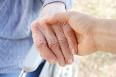 Hand der älteren Frau und helfende Hand Stockfotos