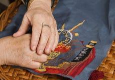 Hand der alten Frau mit einer Nadel und einem Gewinde Lizenzfreie Stockfotos