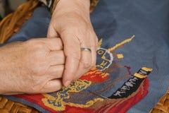 Hand der alten Frau mit einer Nadel und einem Gewinde Lizenzfreies Stockfoto