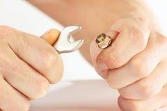 Hand der Arbeitskraft mit einem Schlüssel, zum der Nuss festzuziehen Lizenzfreies Stockbild