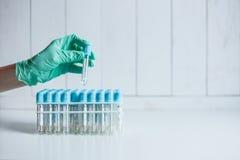 Hand der Arzthelferin am Labor nimmt ein leeres Rohr vom Behälter für das Nehmen des Bluts für Analyse stockfotos