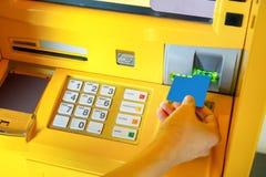 Hand der Asiatin ATM-Karte in ATM-Maschine einfügend stockfotos