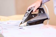 Hand der bügelnden Kleidung der Frau Lizenzfreies Stockfoto