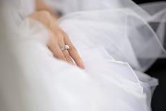 Hand der Braut, die auf Hochzeitskleid legt stockfotos