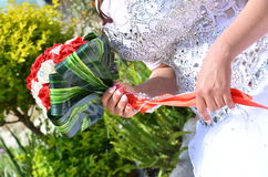 Hand der Braut in einem weißen Kleid mit einem Blumenstrauß des Scharlachrots blüht Lizenzfreie Stockfotografie