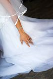 Hand der Braut gegen ihr Kleid Stockfotografie