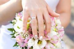 Hand der Braut mit einem Ring auf einer Blumenstraußnahaufnahme Stockbild