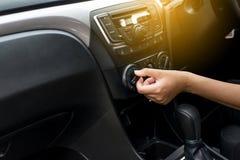 Hand der Frau alte AutoKlimaanlage, Knopf einschaltend auf Armaturenbrett in der Autoplatte lizenzfreie stockbilder