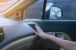 Hand der Frau AutoKlimaanlage einschaltend weil zur Kälte, Knopf auf Armaturenbrett in der Autoplatte lizenzfreie stockfotos