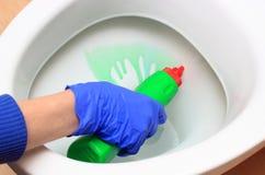 Hand der Frau in der blauen Handschuhreinigungs-Toilettenschüssel Lizenzfreie Stockfotos