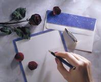 Hand der Frau, die eine Feder schreibt einen Brief anhält Stockfotografie