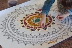 Hand der Frau, die eine Mandala herstellt lizenzfreie stockfotos