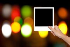 Hand der Frau einen leeren Fotorahmen auf buntem bokeh BAC halten Stockfoto