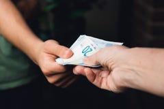 Hand der Frau gibt einem jungen Mann Eurogeld Stockbilder