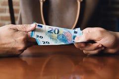 Hand der Frau gibt einem jungen Mann Eurogeld Stockfoto