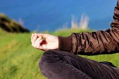 Hand der Frau im Frühjahr meditierend in der Yogahaltung auf Klippen bei Sonnenuntergang lizenzfreie stockfotografie